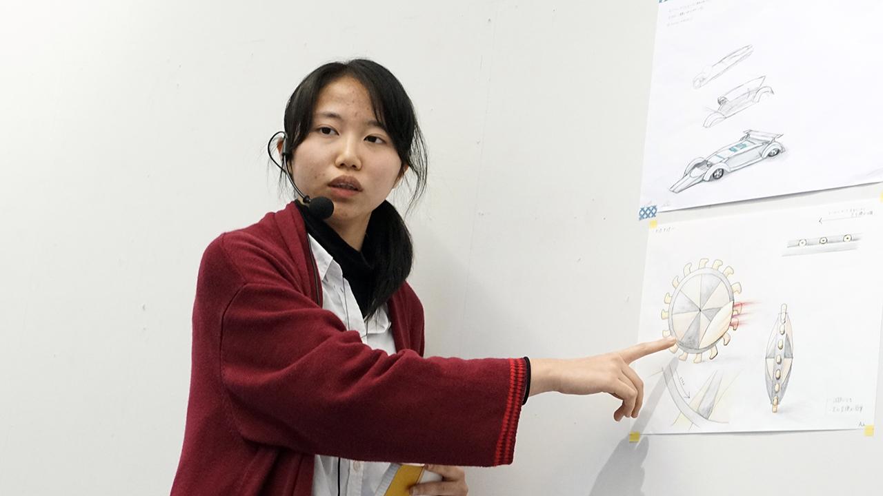 インカムをつけて自分のデザインコンセプトをプレゼンテーションする学生。